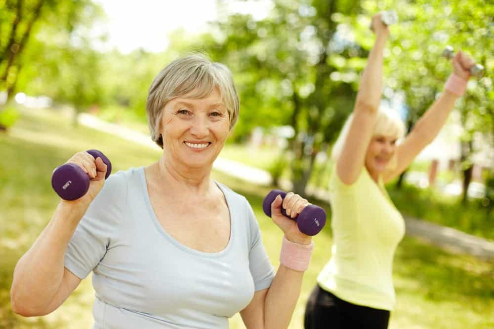 Two senior women lifting weights outside in summer