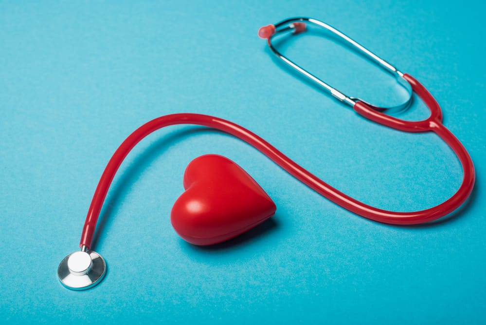 stethoscope and heart-shaped stress reliever on blue background