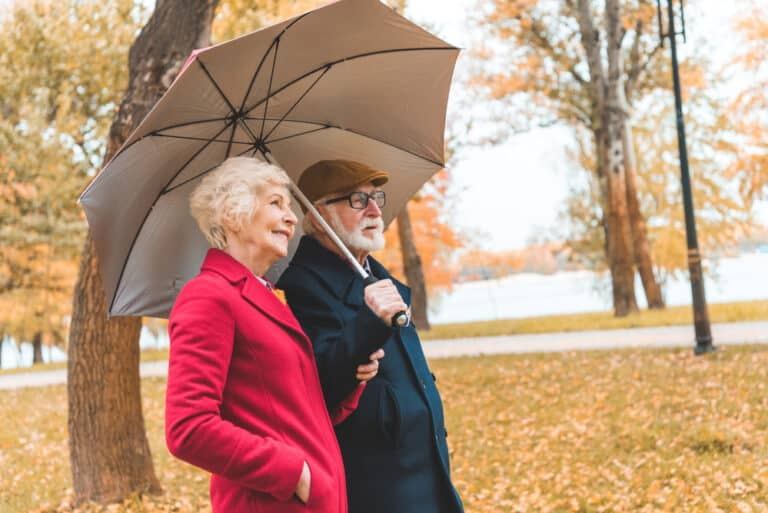 Two seniors on a walk in the park in autumn with an umbrella