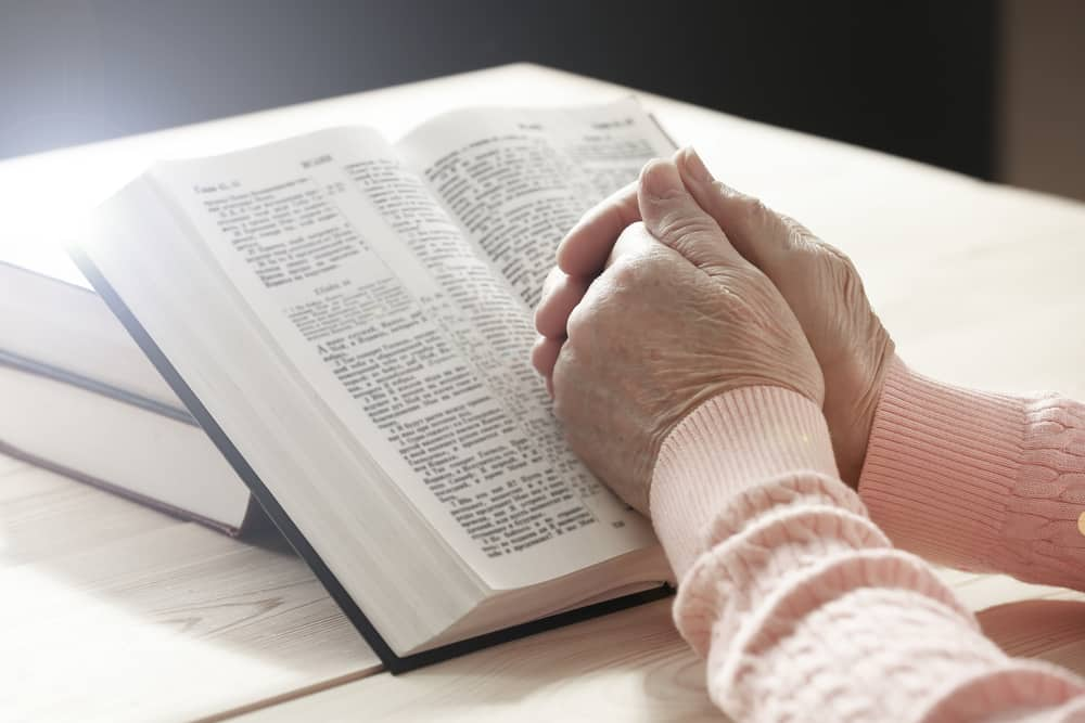Senior hands clasped on top of open bible
